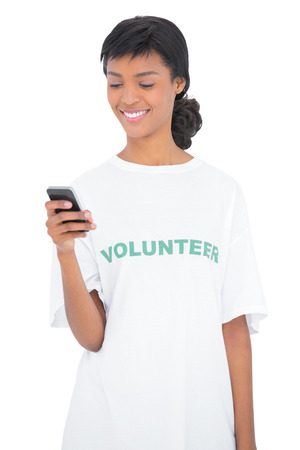 Pretty black haired volunteer texting with her mobile phone on white background photo