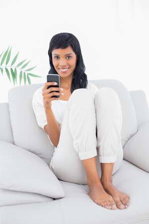 Delighted black haired woman in white clothes typing on her mobile phone in a living room photo
