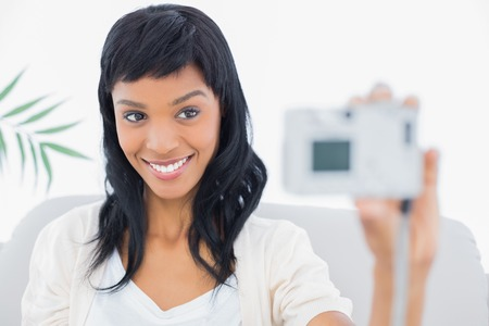 Natural black haired woman in white clothes taking a picture of herself in a living room Stock Photo