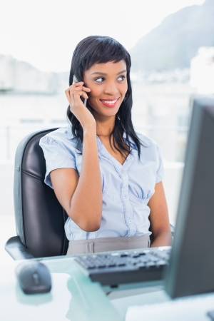 Happy businesswoman calling someone with her mobile phone in office photo