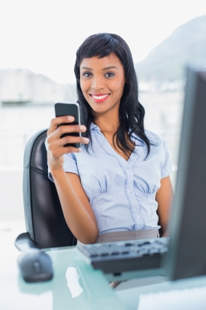 Charming businesswoman holding a mobile phone in office