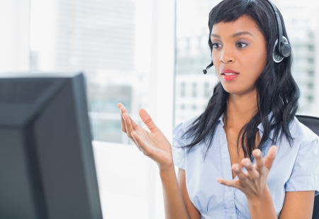 confused woman: Confused operator looking at her computer in office