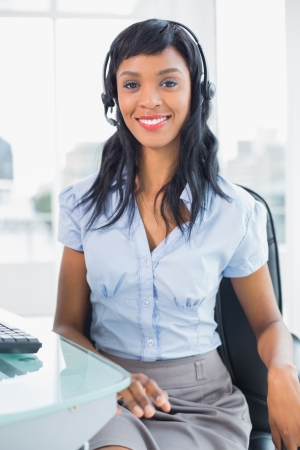 Stylish operator smiling and looking at camera in office photo