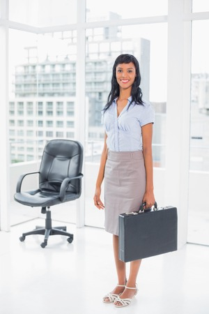 Pretty businesswoman holding a suitcase in office photo