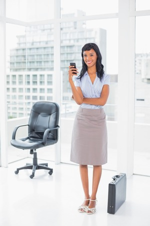 Happy businesswoman texting on her mobile phone in office photo