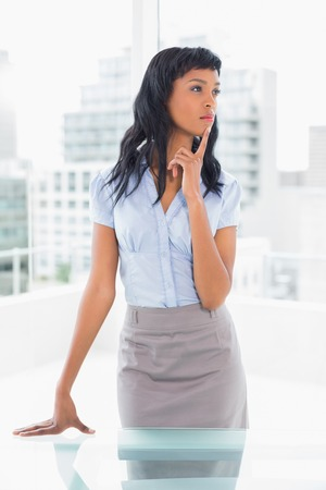 Pensive businesswoman standing at her desk in office photo