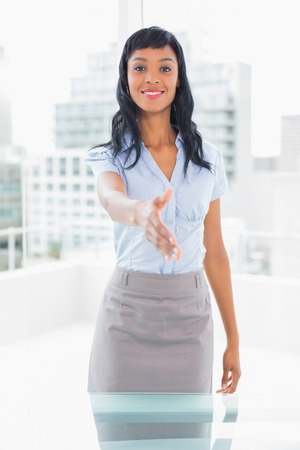 Pleased businesswoman presenting her hand in office photo