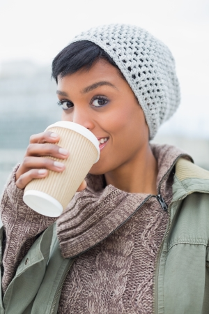 Pleased young model in winter clothes enjoying coffee outside on a cloudy day photo