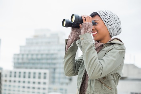 Smiling young model in winter clothes watching with binoculars outside on a cloudy day photo