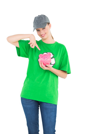 Smiling pretty environmental activist showing a piggy bank on white background photo