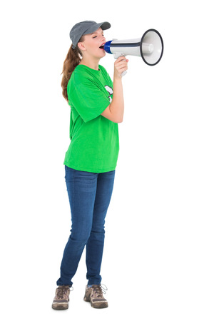 Motivated pretty environmental activist shouting in a megaphone on white background photo