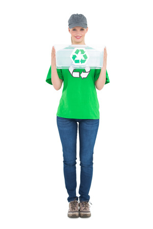 Happy pretty environmental activist holding a recycling box on white background photo