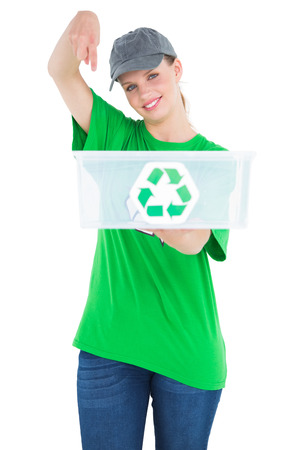 Cheerful pretty environmental activist showing a recycling box on white background photo