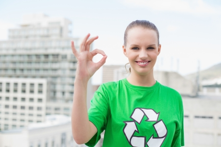 Natural pretty environmental activist making okay gesture on city background photo