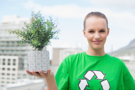 Happy pretty environmental activist showing a plant on city background photo
