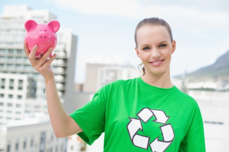 Content pretty environmental activist holding a piggy bank on city background photo