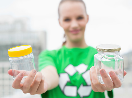 Pleased pretty environmental activist offering two jars on city background photo