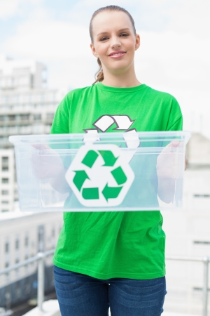 Pleased pretty environmental activist holding a recycling box on city background photo