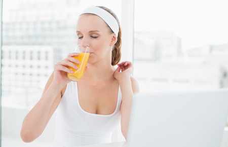 Natural pretty sportswoman enjoying orange juice in a bright room photo