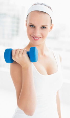 Dynamic pretty sportswoman carrying a dumbbell in a bright room photo