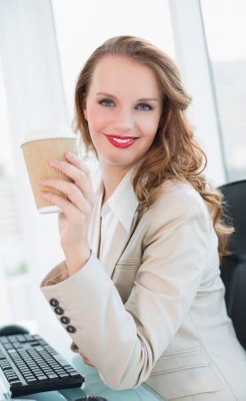 Smiling pretty businesswoman having a cup of coffee at office photo