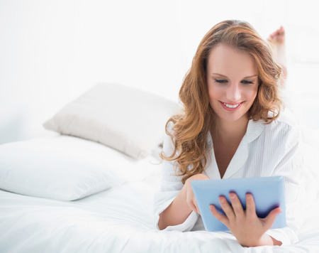Cheerful pretty woman using a tablet pc lying on her bed in a bedroom photo