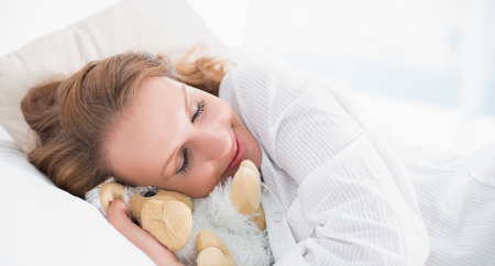 Smiling pretty woman sleeping embracing a plush sheep in a bedroom photo