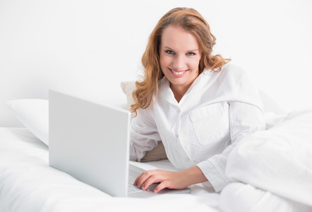 Relaxed pretty woman using a laptop lying on her bed in a bedroom photo