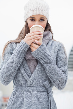 Pretty brunette with winter clothes on drinking coffee outdoors on a cold grey day photo