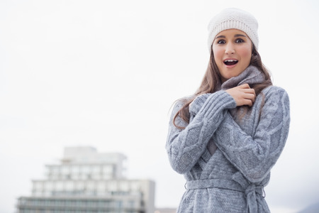 Surprised young woman with winter clothes on posing outdoors on a cold grey day photo