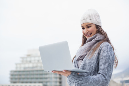 Cheerful woman with winter clothes on using her laptop outdoors on a cold grey day photo