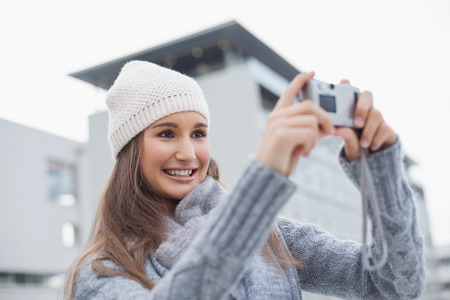 Smiling gorgeous woman with winter clothes on taking a self picture outdoors on a cold grey day photo