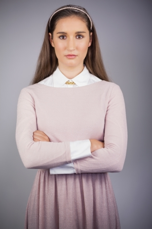 Stern young model with pink dress on posing on grey background photo