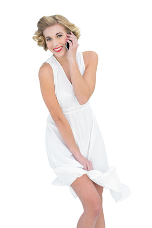 Amused fashion blonde model making a phone call on white background photo