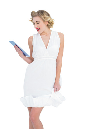 Delighted fashion blonde model looking at a tablet pc on white background photo