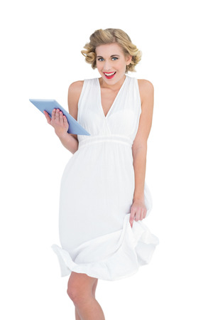 Amused fashion blonde model holding a tablet pc on white background photo