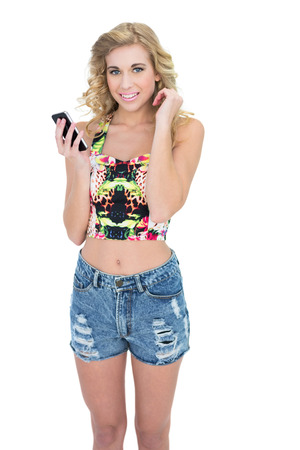 Cheerful retro blonde model using a mobile phone on white background photo