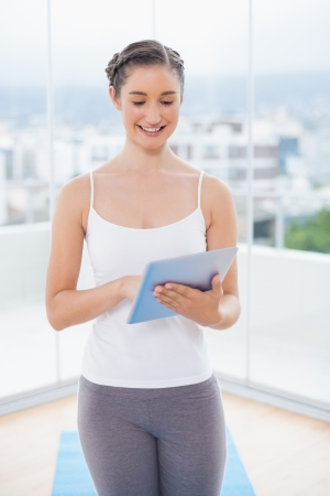 scrolling: Smiling sporty model scrolling on tablet pc in bright fitness studio