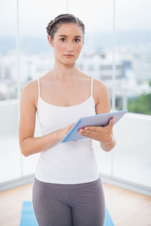 scrolling: Serious sporty model in bright fitness studio scrolling on tablet pc