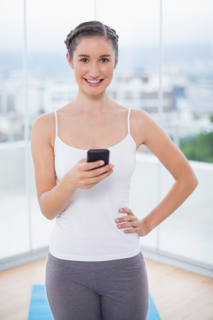 Smiling sporty brunette text messaging in bright fitness studio photo