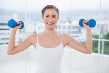 Happy sporty brunette exercising with dumbbells in bright fitness studio photo