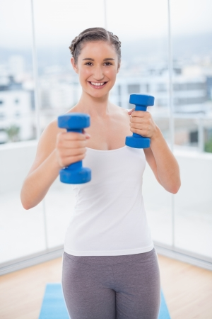 Cheerful athletic brunette exercising with dumbbells in bright fitness studio photo