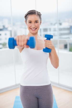 Smiling athletic brunette exercising with dumbbells in bright fitness studio photo