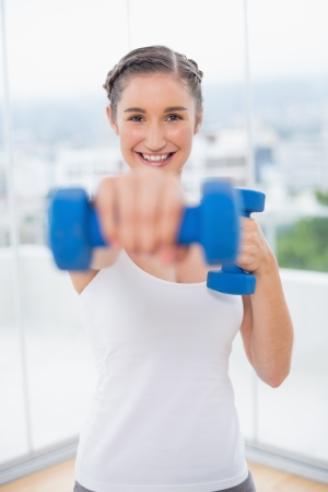 Happy athletic brunette exercising with dumbbells in bright fitness studio photo