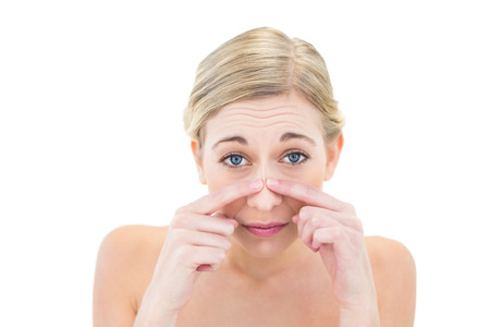 Frowning young blonde woman touching her nose on white background photo