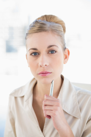 Meditative young blonde businesswoman looking at camera at office Stock Photo - 22326422