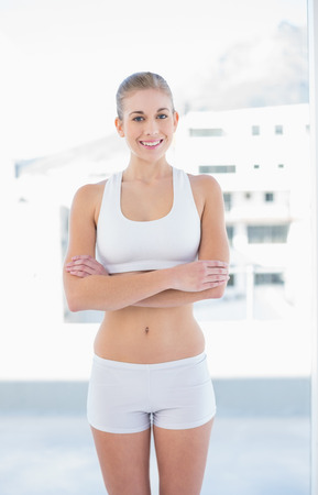 Cheerful young blonde model in white sportswear posing with crossed arms photo