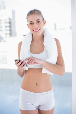 Content young blonde model in white sportswear using her mobile phone Stock Photo