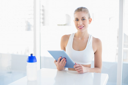 Charming young blonde model in white sportswear using a tablet pc Stock Photo - 22326575