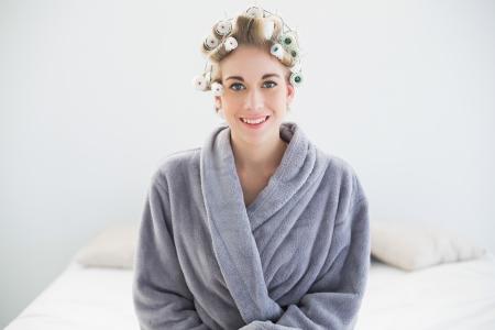 Très détendu femme blonde en bigoudis posant dans une chambre à coucher Banque d'images